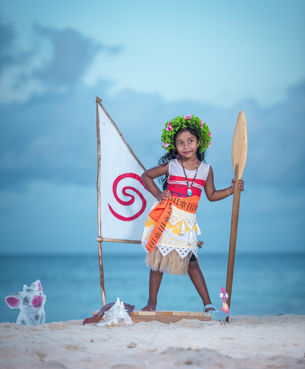 woman in red and white dress holding brown wooden stick standing on white sand during daytime