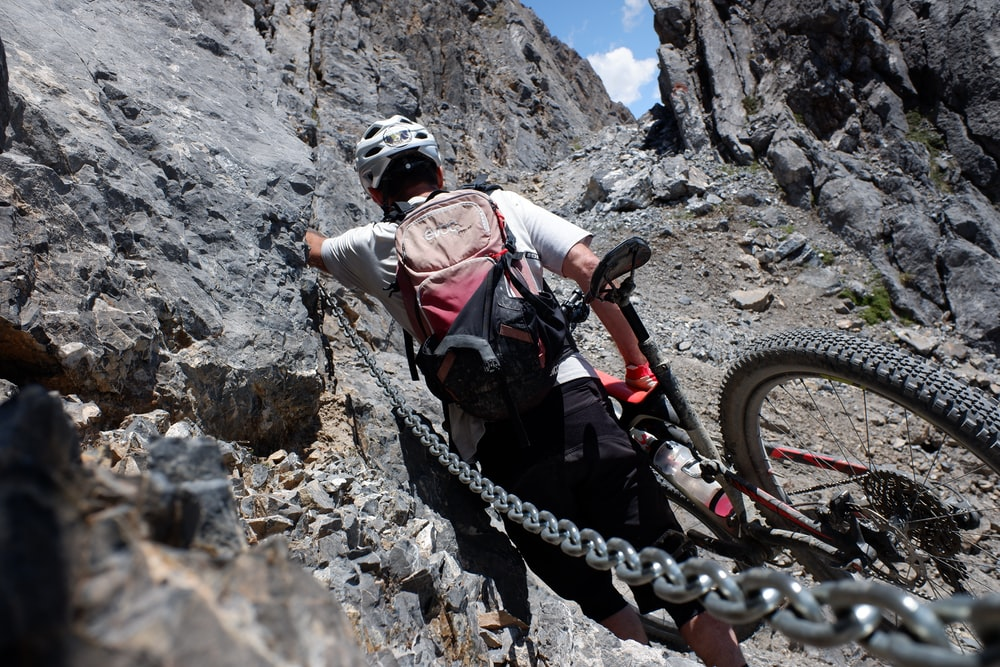 man in white shirt and black pants with black helmet climbing mountain during daytime