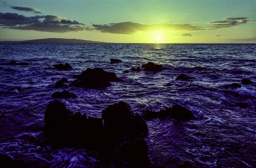 black rocks on sea under blue sky during daytime