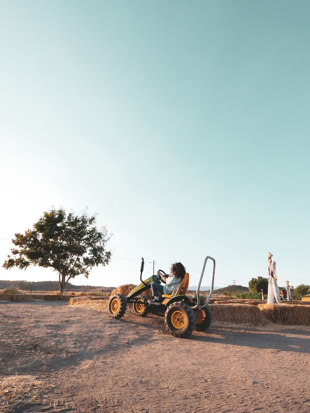 man in green shirt riding on yellow and black dune buggy