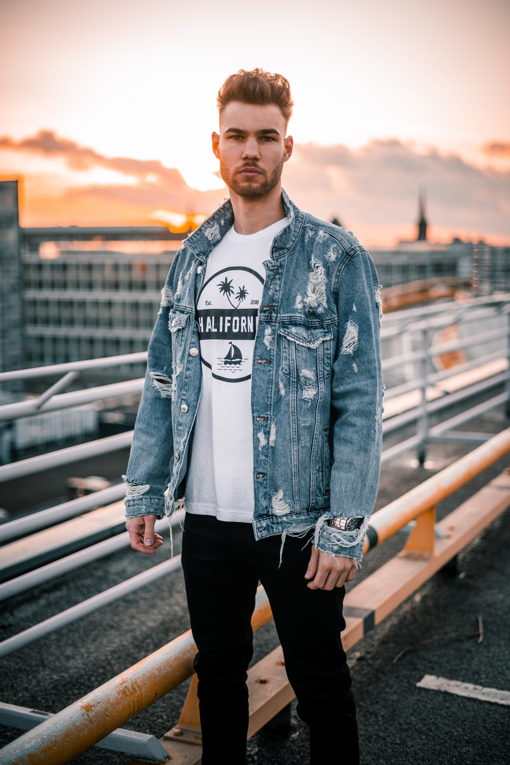 man in blue denim jacket standing on bridge during daytime