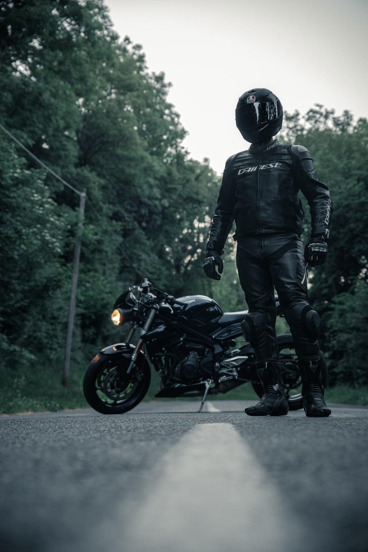 man in black jacket and helmet riding black motorcycle
