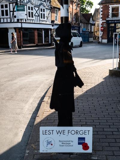 woman in black coat standing on sidewalk during daytime