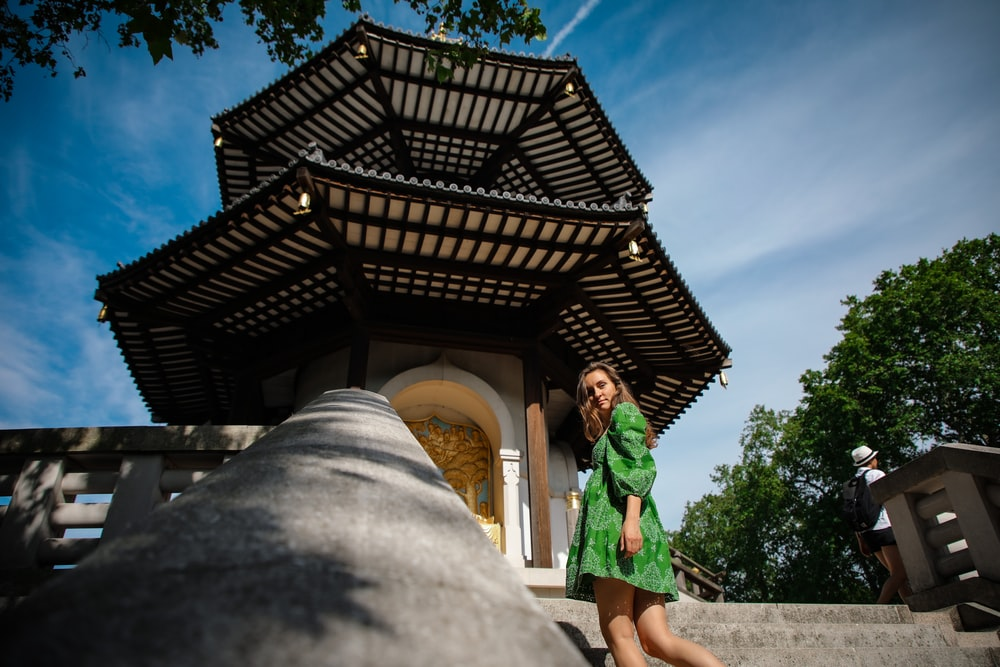 woman in green dress standing near brown wooden house during daytime