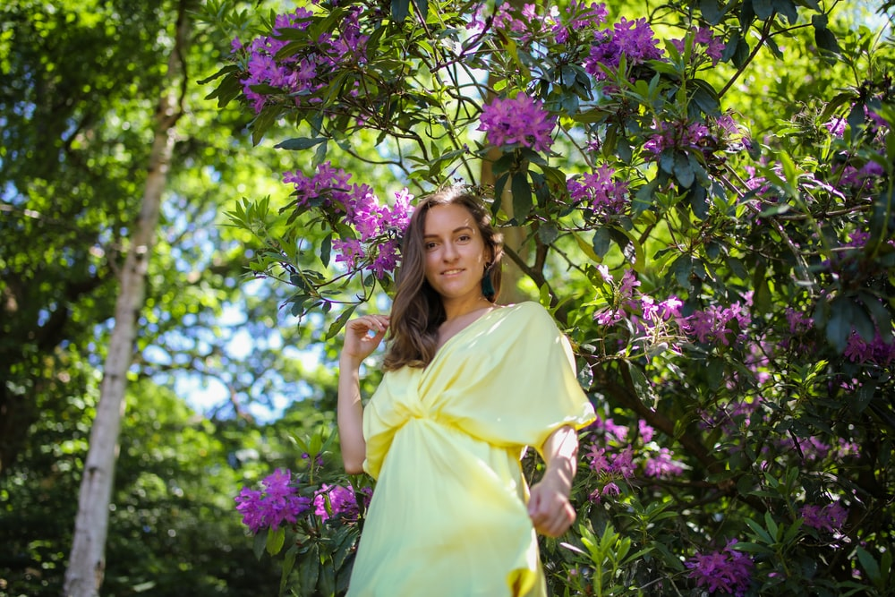 woman in yellow dress standing beside purple flowers during daytime