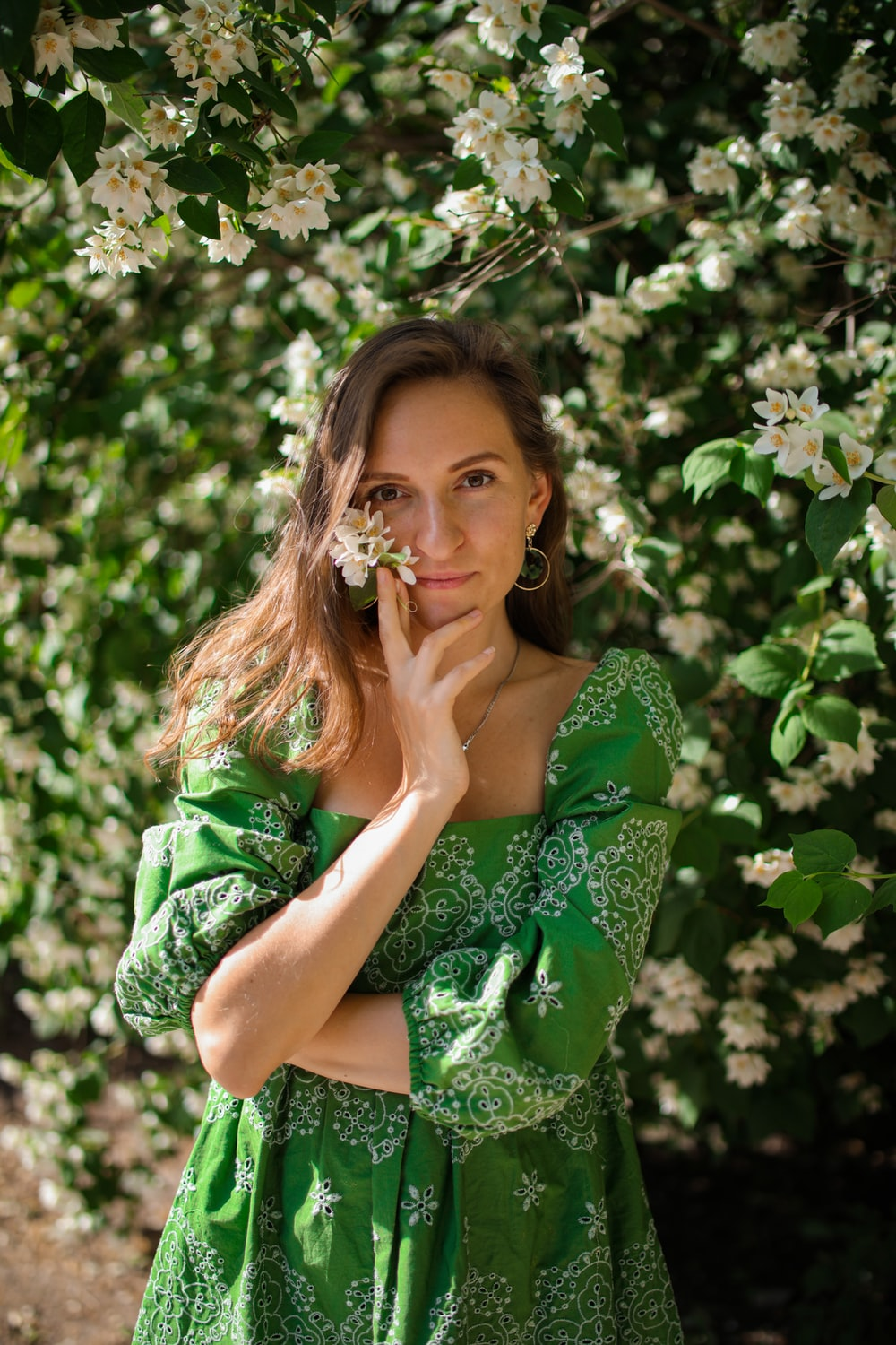 woman in green and white floral dress sitting on green grass during daytime