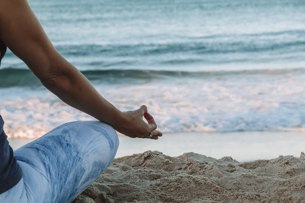 person in blue shorts sitting on beach shore during daytime