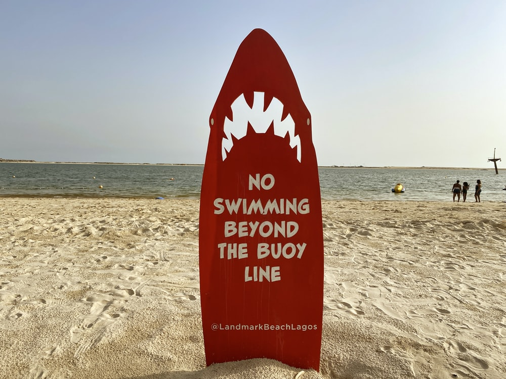 red and white beach signage on beach during daytime