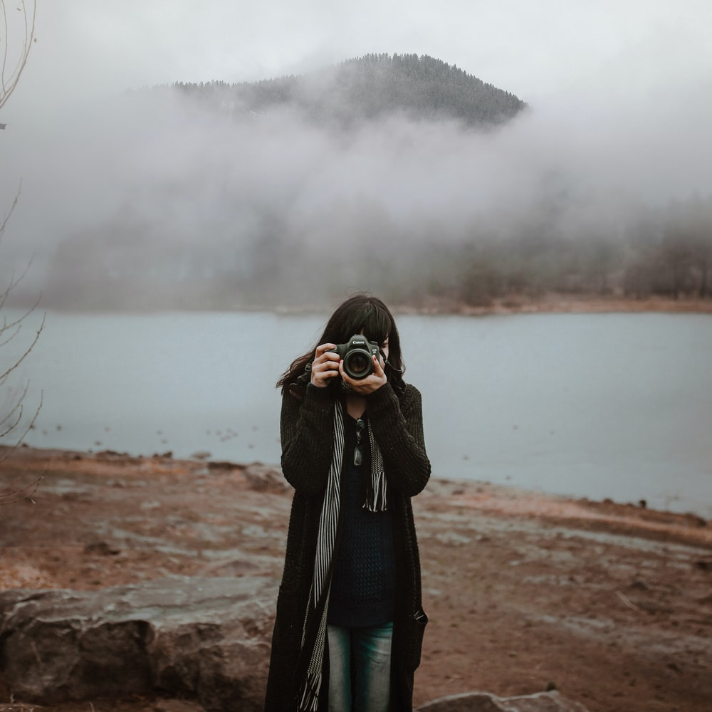 woman in black coat standing on brown field
