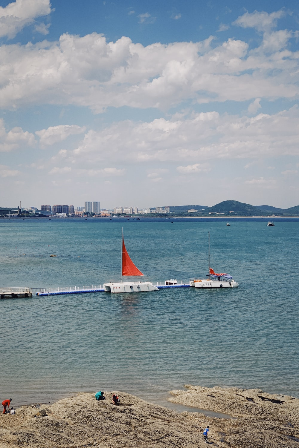 white and red sail boat on sea during daytime