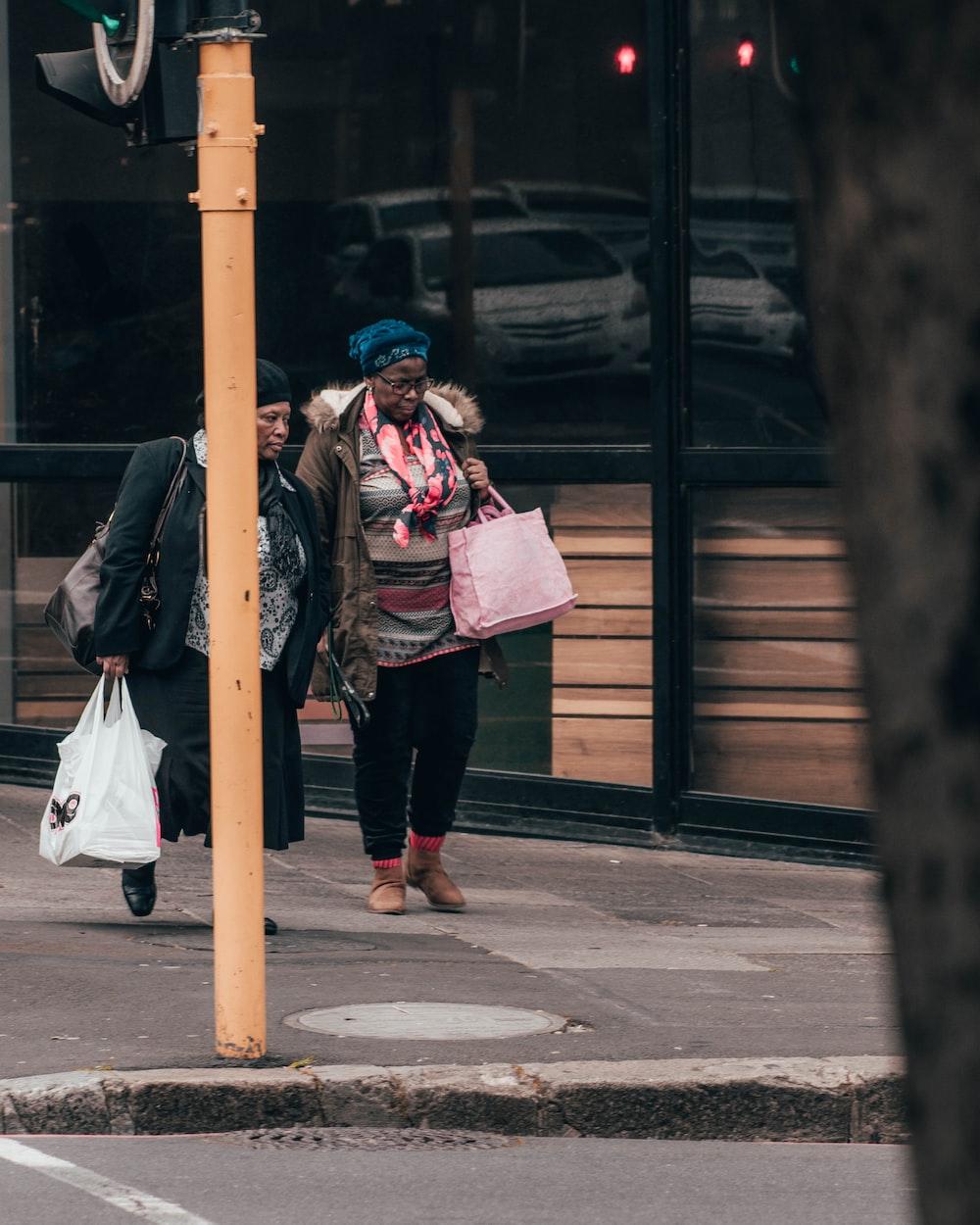 woman in black jacket and black pants carrying pink backpack walking on sidewalk during daytime