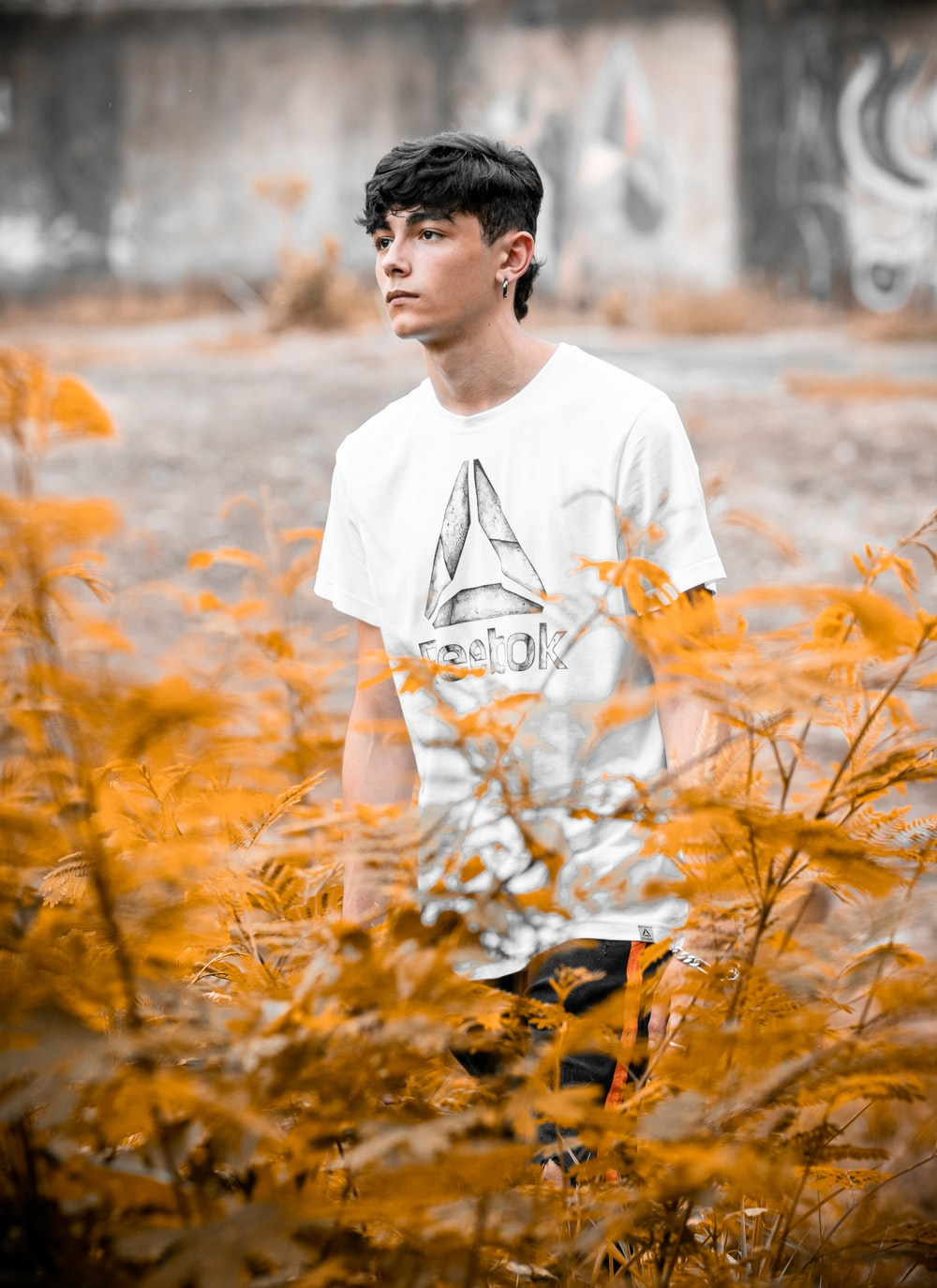 man in white crew neck t-shirt standing on brown grass field during daytime