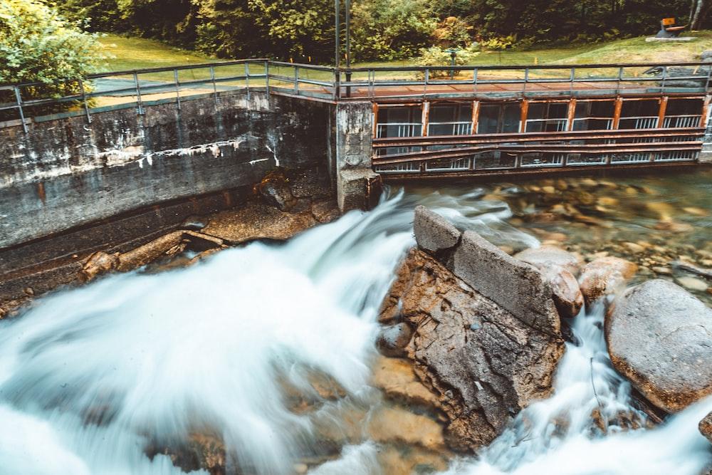 water falls on brown wooden bridge