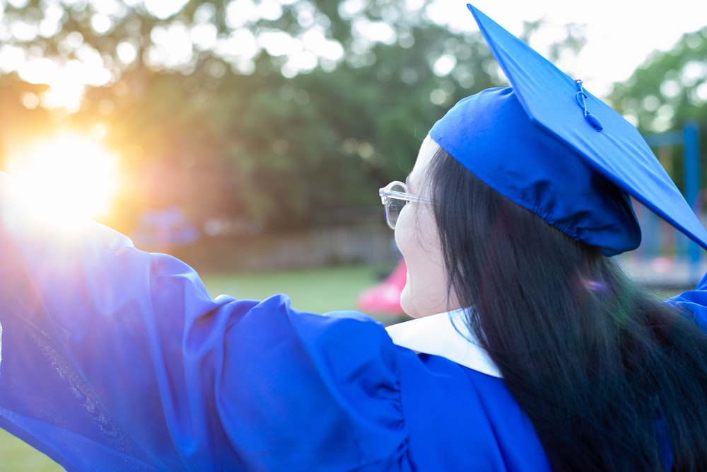 woman in blue academic dress wearing blue academic hat