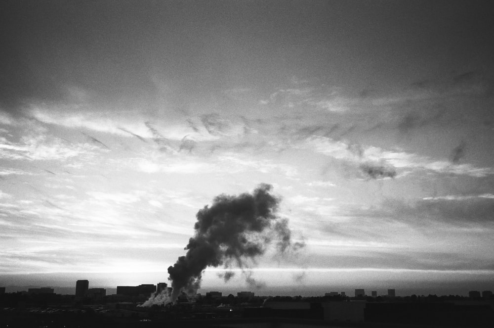 grayscale photo of smoke coming from factory