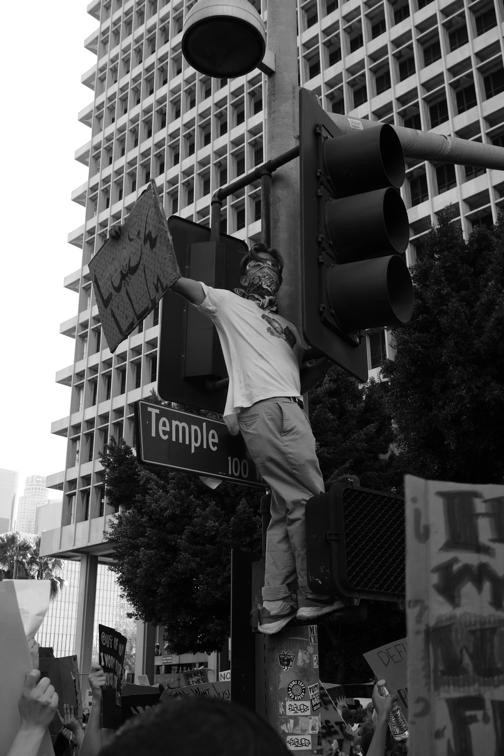 man in black suit jacket and pants standing on traffic light in grayscale photography