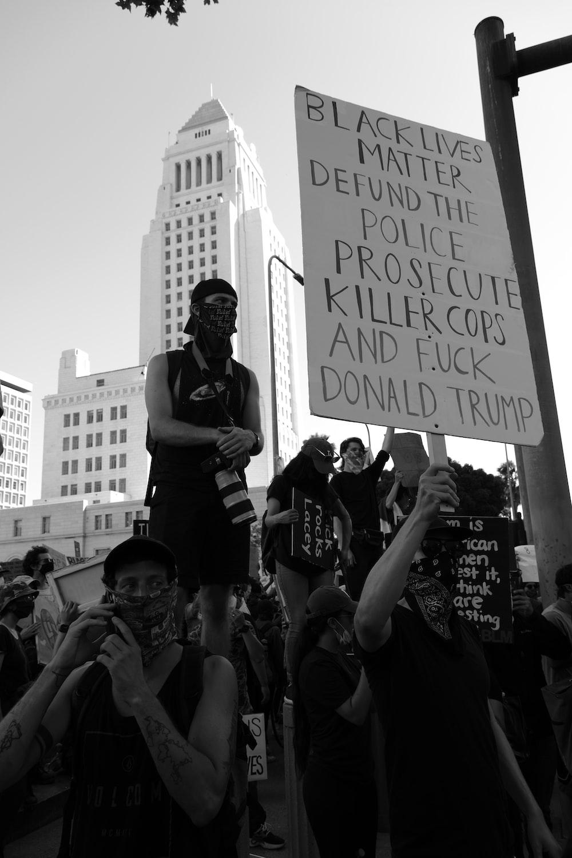 grayscale photo of man holding signage