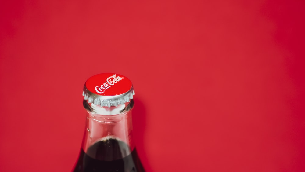 coca cola bottle on red surface