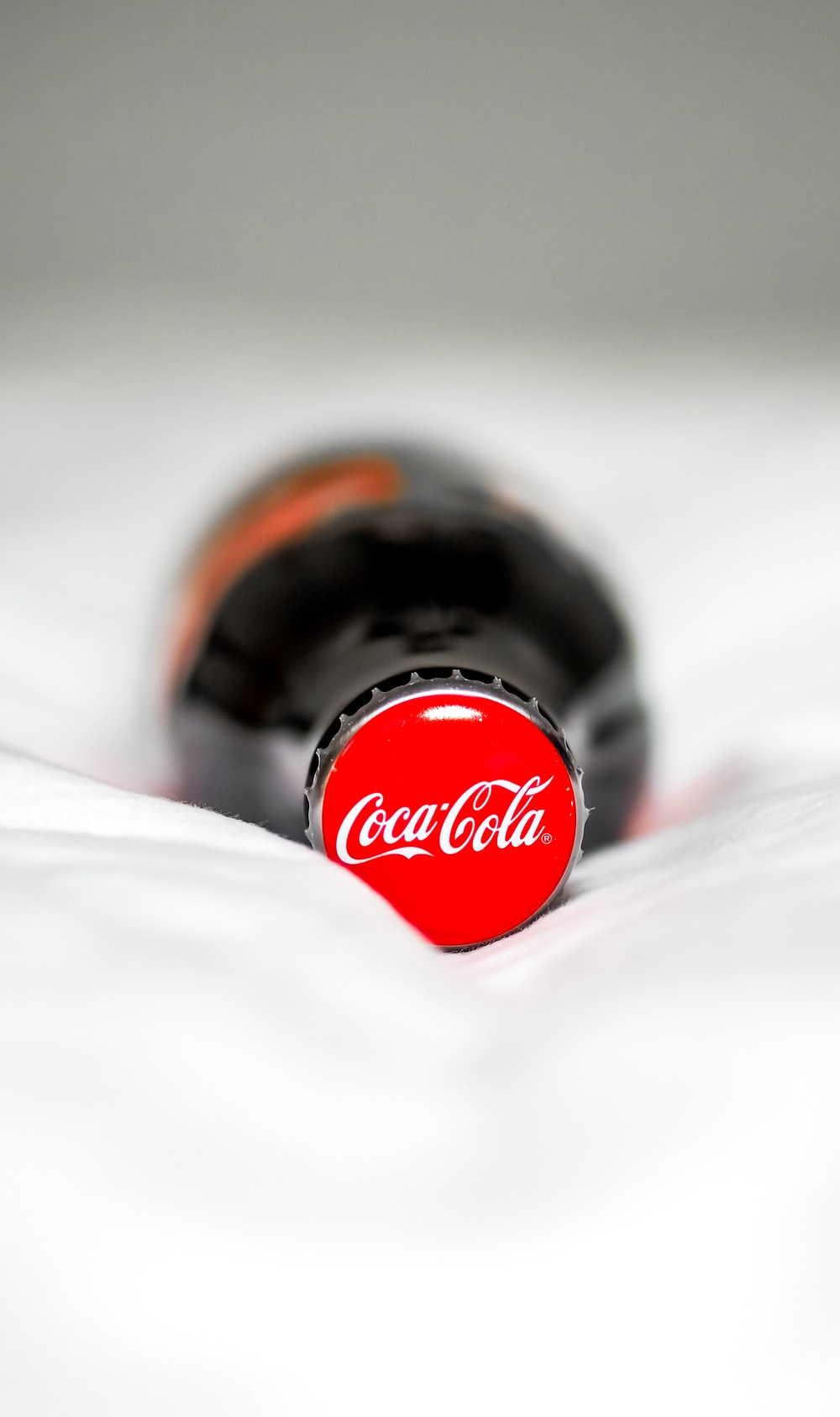 coca cola bottle on white textile