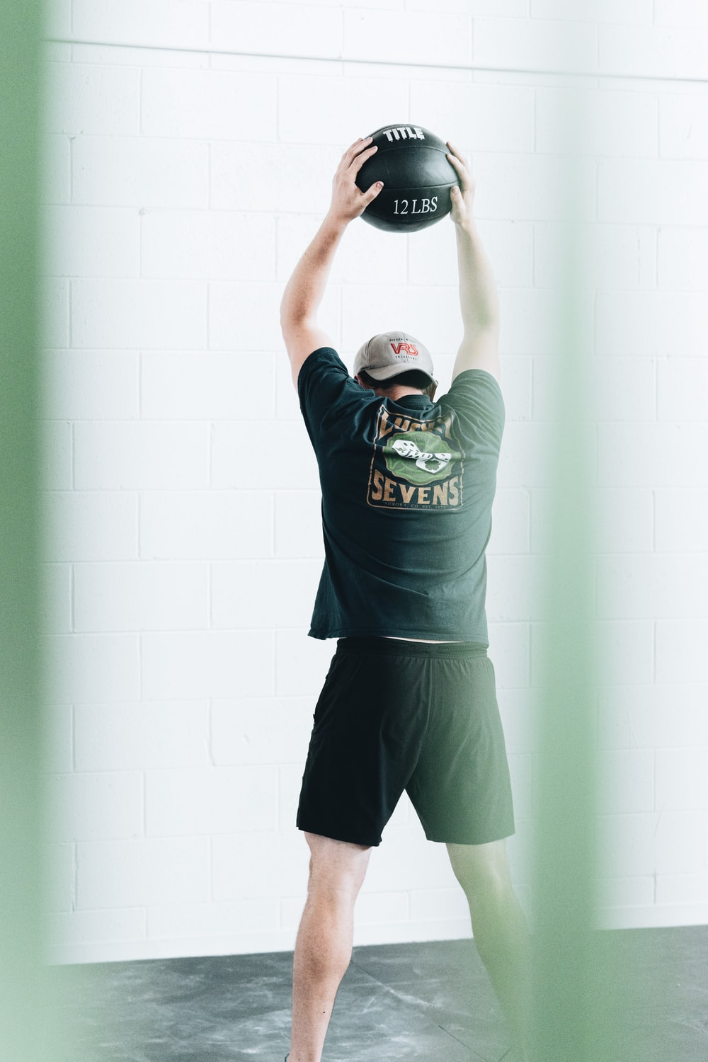 man in green crew neck t-shirt and black shorts holding black and white basketball