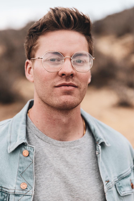 man in blue denim button up jacket wearing black framed eyeglasses
