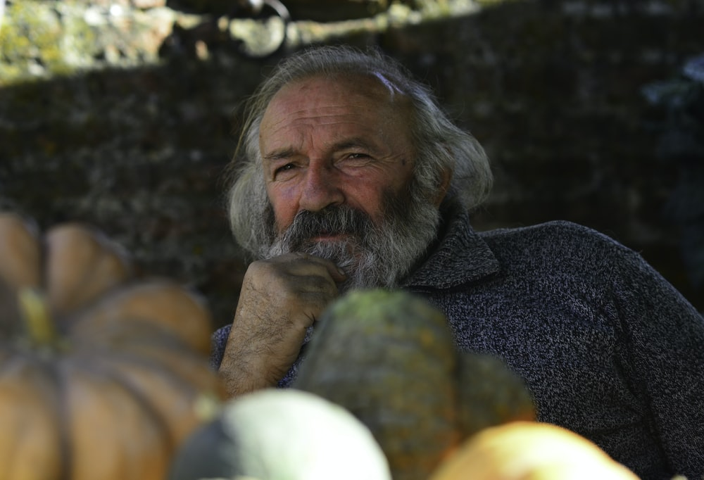 man in gray shirt with white beard surrounded by yellow and green round fruits