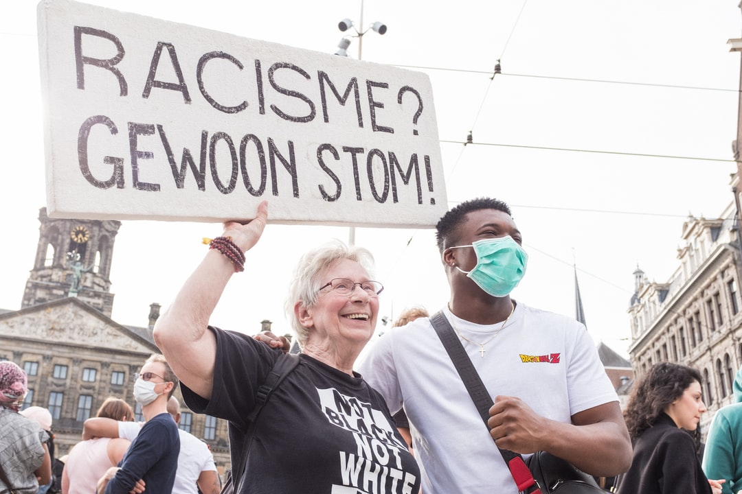 Black Lives Matter Protest. Old Woman With Young Black Man Smiling  - unsplash