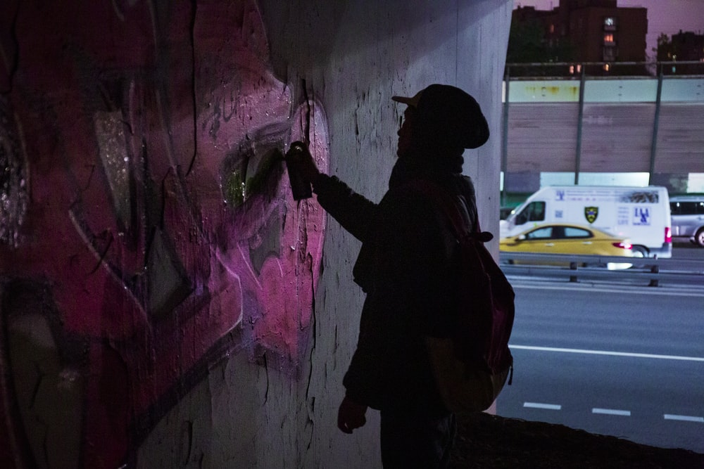 man in black jacket and black pants standing beside wall with graffiti during daytime