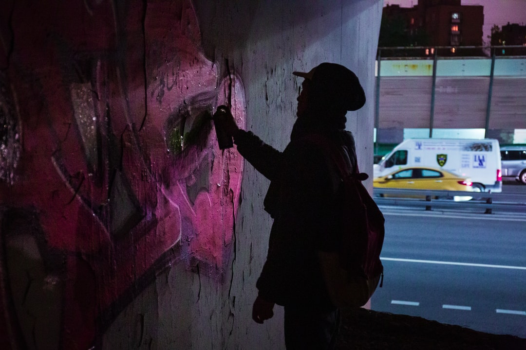 Man In Black Jacket and Black Pants Standing Beside Wall With Graffiti During Daytime - unsplash
