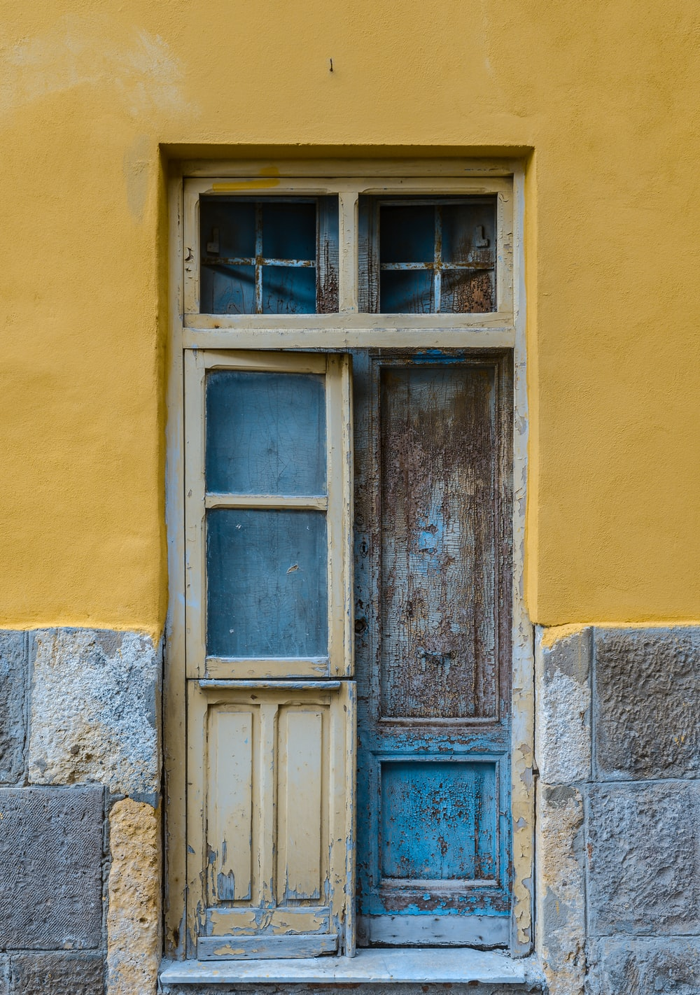 blue wooden window on yellow concrete wall