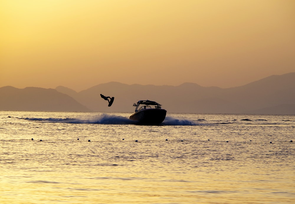 black and white boat on sea during sunset