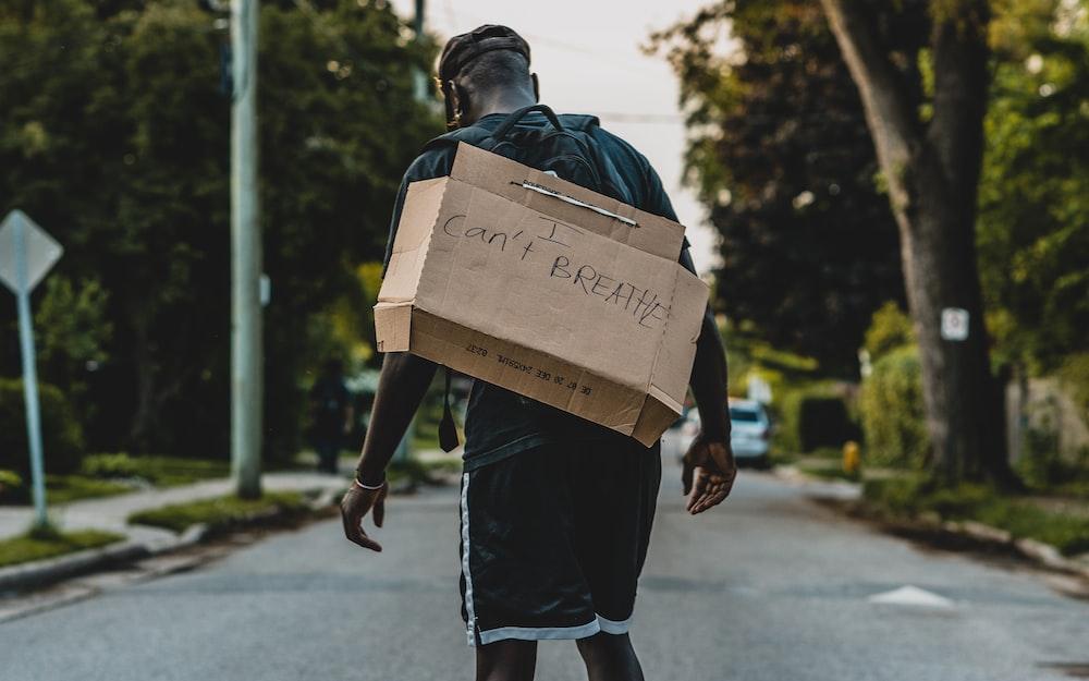 man in black jacket carrying brown cardboard box