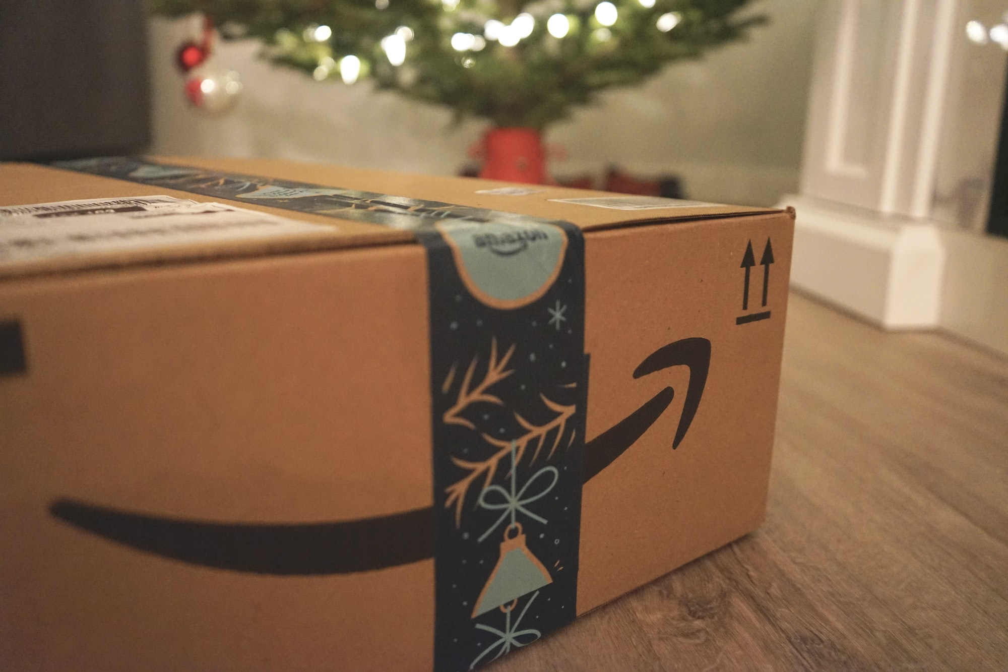 Amazon delivery box with gifts in front of a Christmas tree.