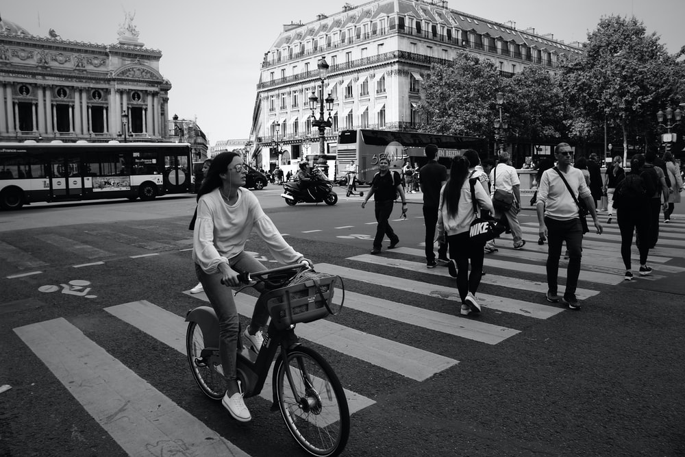 man in white t-shirt riding bicycle on pedestrian lane in grayscale photography