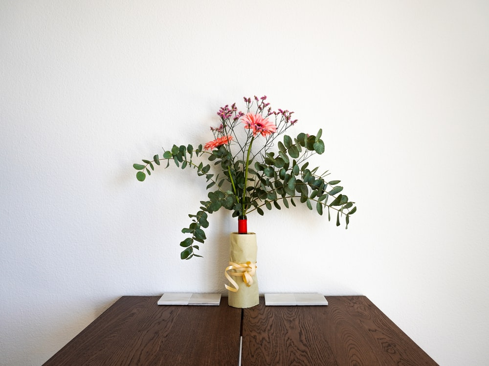red flowers in white ceramic vase on brown wooden table