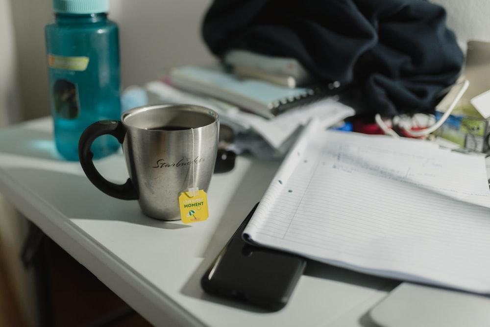 black and silver ceramic mug on white table