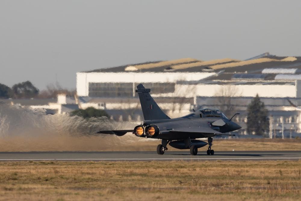 black fighter jet on brown field during daytime