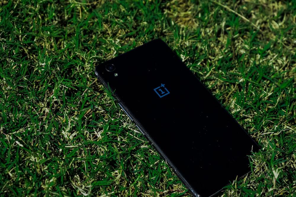 black iphone 5 on green grass