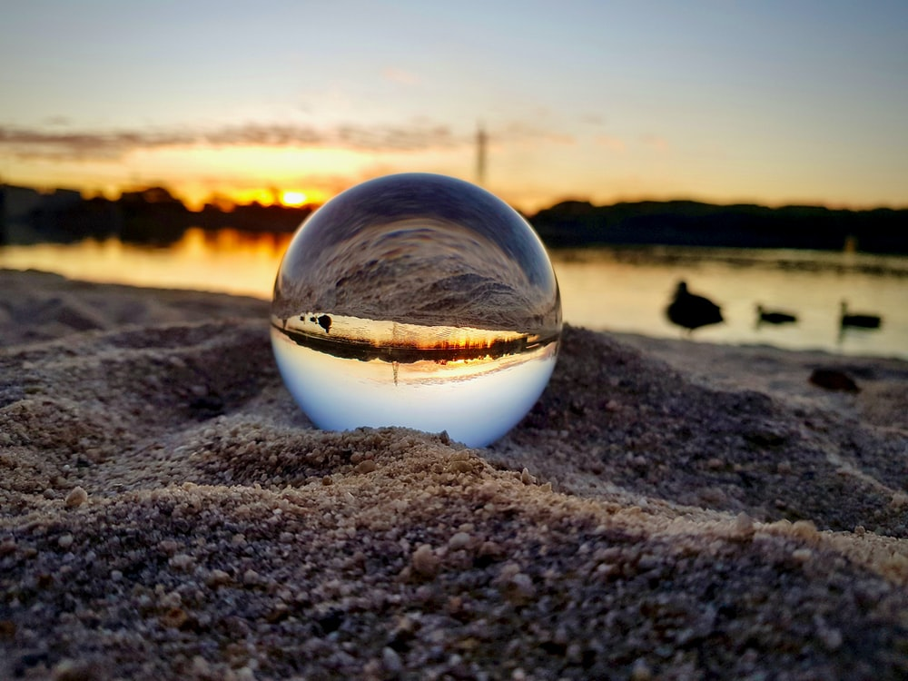 clear glass ball on brown sand during sunset