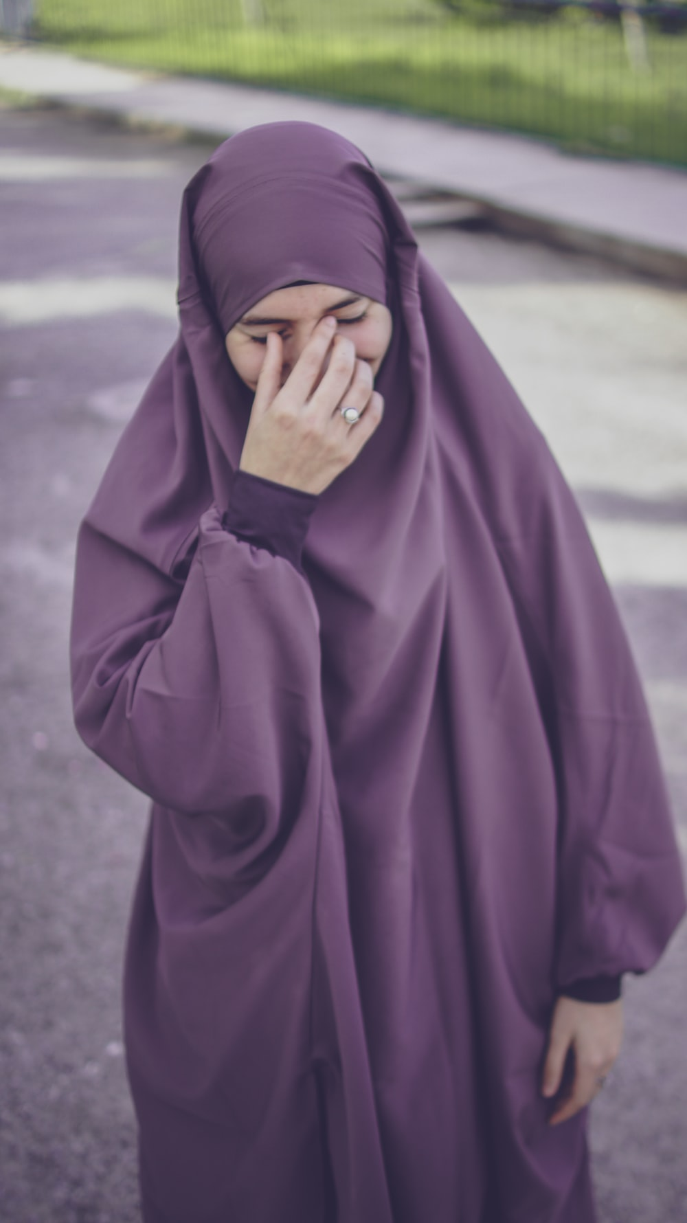 woman in purple hijab covering her face with purple textile