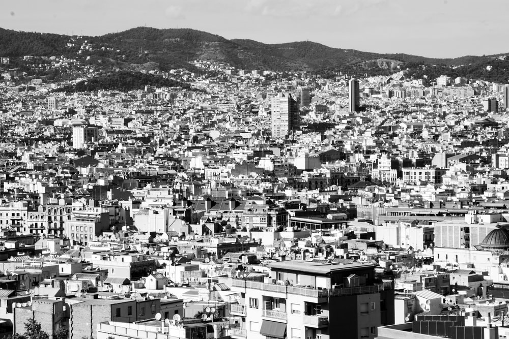 grayscale photo of city buildings near mountain