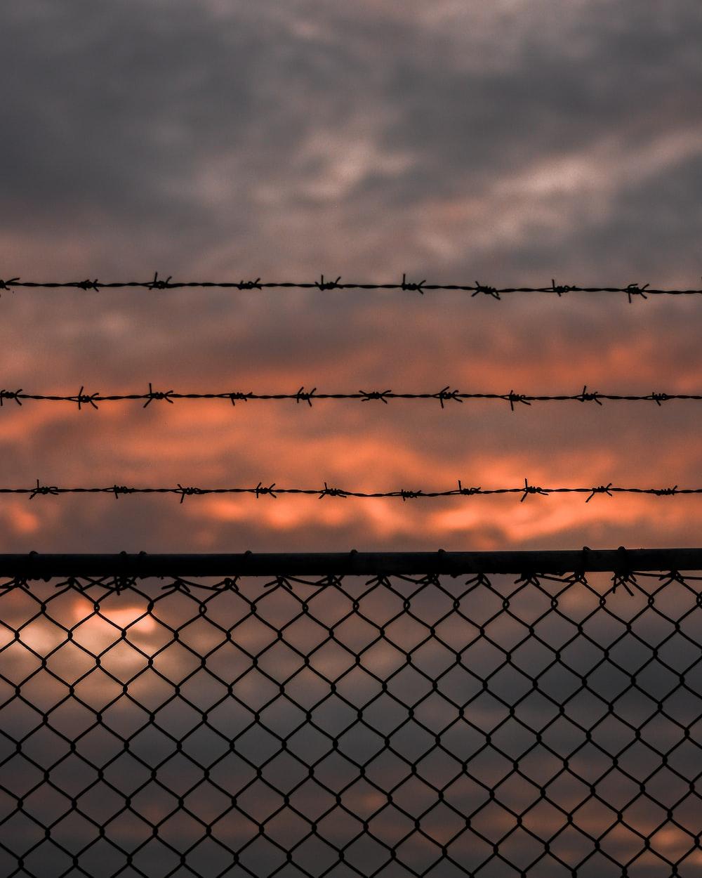 grey metal fence under grey clouds
