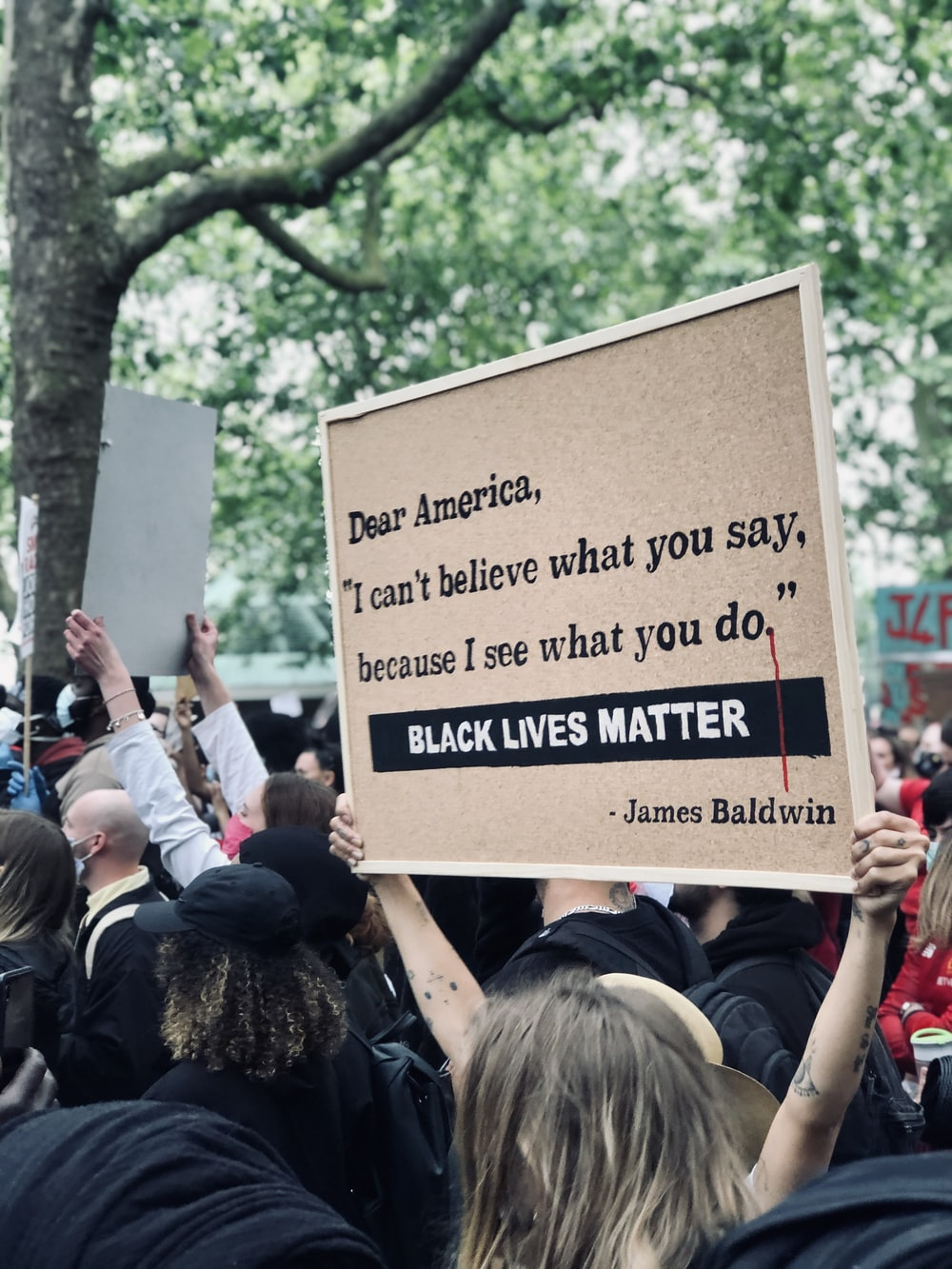 people holding brown and black quote board during daytime