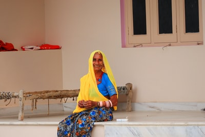 Raipur woman in yellow hijab sitting on white wooden table