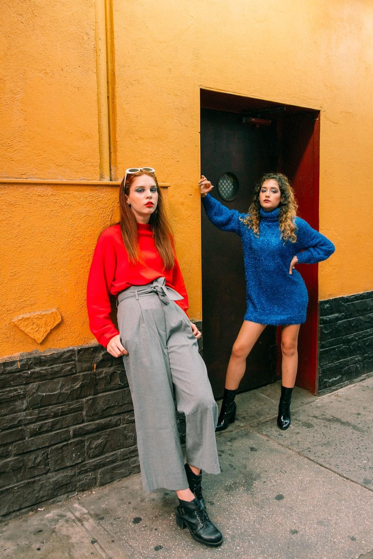 2 women standing beside brown wooden door