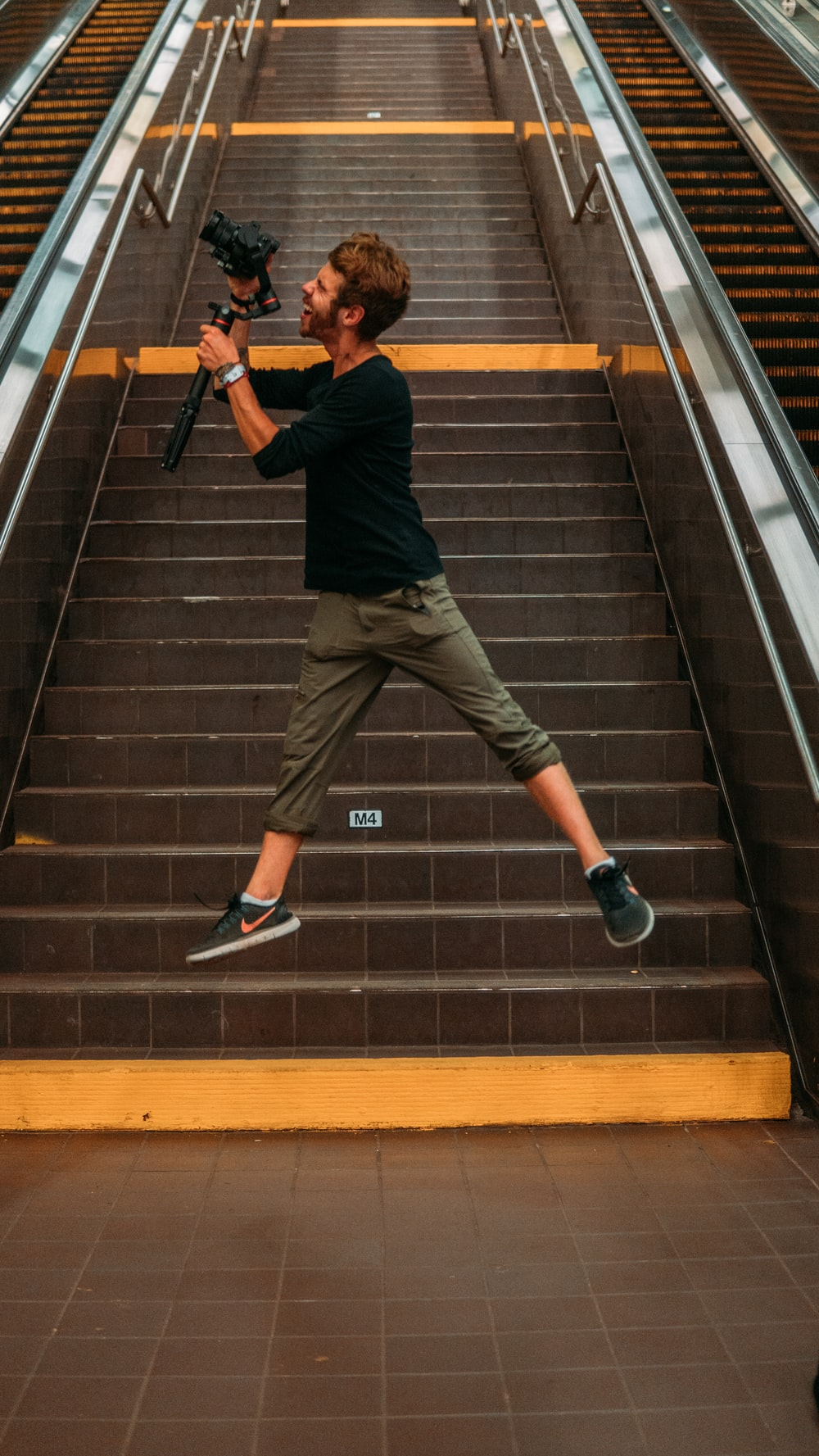 man in black t-shirt and brown pants walking on black and brown staircase