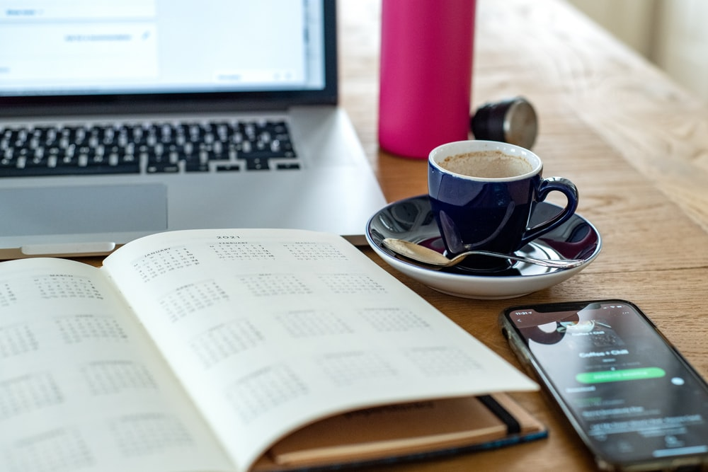 black and white ceramic mug on saucer beside macbook pro