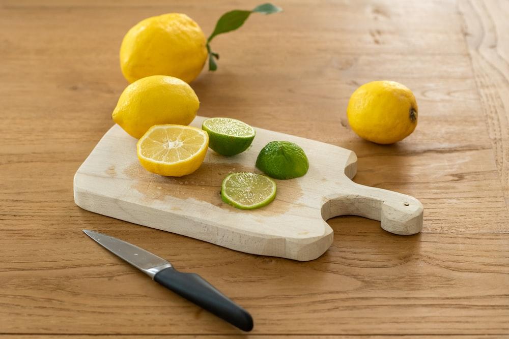 sliced lemon beside knife on brown wooden chopping board