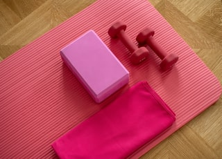 pink dumbbell on pink textile