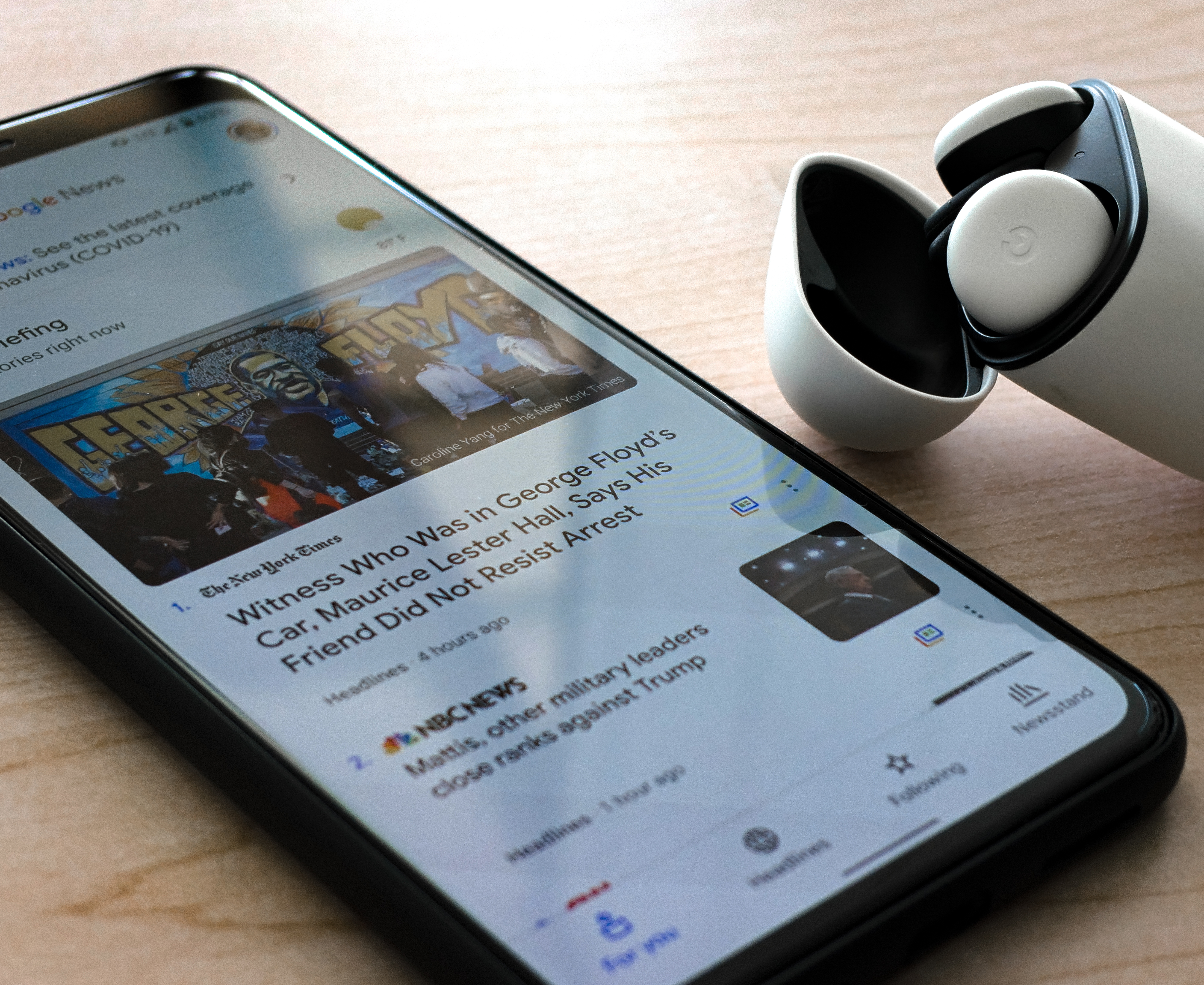 A Google Pixel 4 XL displays news of the Nationwide Protests while resting next to a pair of Pixel Buds